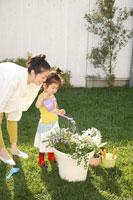庭のお花に水をやる日本人の母親と娘