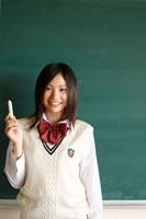 黒板の前に立つ日本人の女子高校生