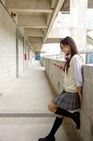 廊下で携帯電話を持つ日本人の女子高校生