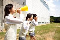 校庭でメガホンを持って応援する女子高校生