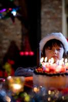 サンタの帽子をかぶったハーフの男の子とケーキ