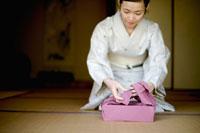 風呂敷を包む和服の女性