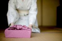 風呂敷包みを差し出す和服の女性