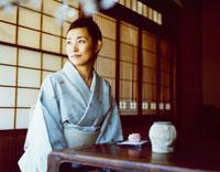 日本茶と和菓子を前にする和服の女性