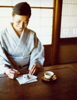 日本茶と和菓子をいただく和服の女性