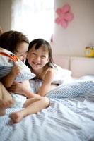ベッドでくつろぐ男の赤ちゃんと女の子