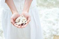 波打ち際で貝とサンゴを手に載せる女性の手