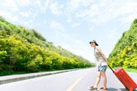 スーツケースをひき道路を渡る女性