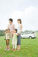 シャボン玉が舞う中で車をバックに立つ家族