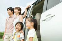 車の前に立って笑う日本人家族