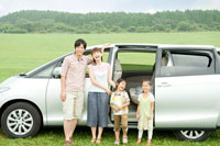 車の前に立って笑う日本人家族のポートレイト