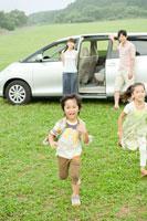 車から駆け出す子供達とそれを見つめる両親