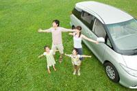 草原で車のそばで深呼吸をする日本人家族