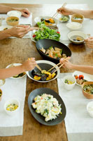 料理を箸でつかもうとする日本人家族