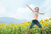ひまわり畑でジャンプをする少年