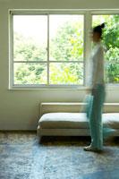 窓辺のソファの前を歩く女性のシルエット