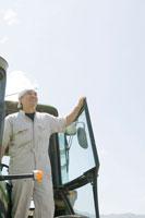 トラクターから空を見上げる酪農家