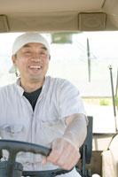 トラクターを運転する酪農家