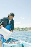 バケツに水を汲む漁師