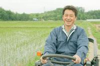 トラクターを運転しながら笑う農夫