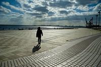 沿岸を歩く女性