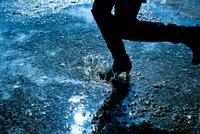 水たまりを歩く女性の足元