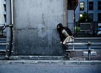 都会の街で身をひそめる女性