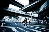 横断歩道を歩く女性と高速道路