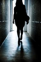 出口に向かって歩く女性の後ろ姿のシルエット