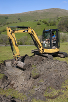 Farmer repairing old blocked drain in upland meadow using mi