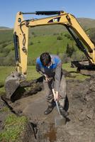 Farmer repairing old blocked drain in upland meadow using mi 32259008581| 写真素材・ストックフォト・画像・イラスト素材|アマナイメージズ