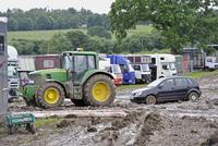 John Deere 6930 tractor pulling car out of muddy carpark at