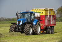 New Holland tractor with Pottinger forage wagon, picking up