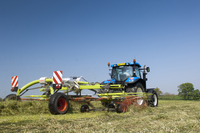 New Holland tractor with Claas grass rake, rowing grass up i
