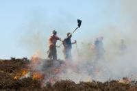 Firemen attemting to control heather moor burning on shootin