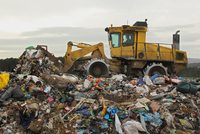 Compactor moving rubbish on landfill tip, Dorset, England, F