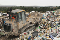 Bulldozer moving rubbish on landfill tip, Dorset, England, F