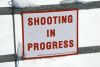 Shooting In Progress' sign tied to gate in snow, warning of