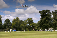Cricket match being played on village pitch, on summer after