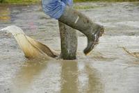 ブーツをはいて泥水の中を歩く人
