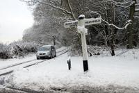 雪道を走る車と道路標識