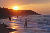 日の出と磯釣りをする人々