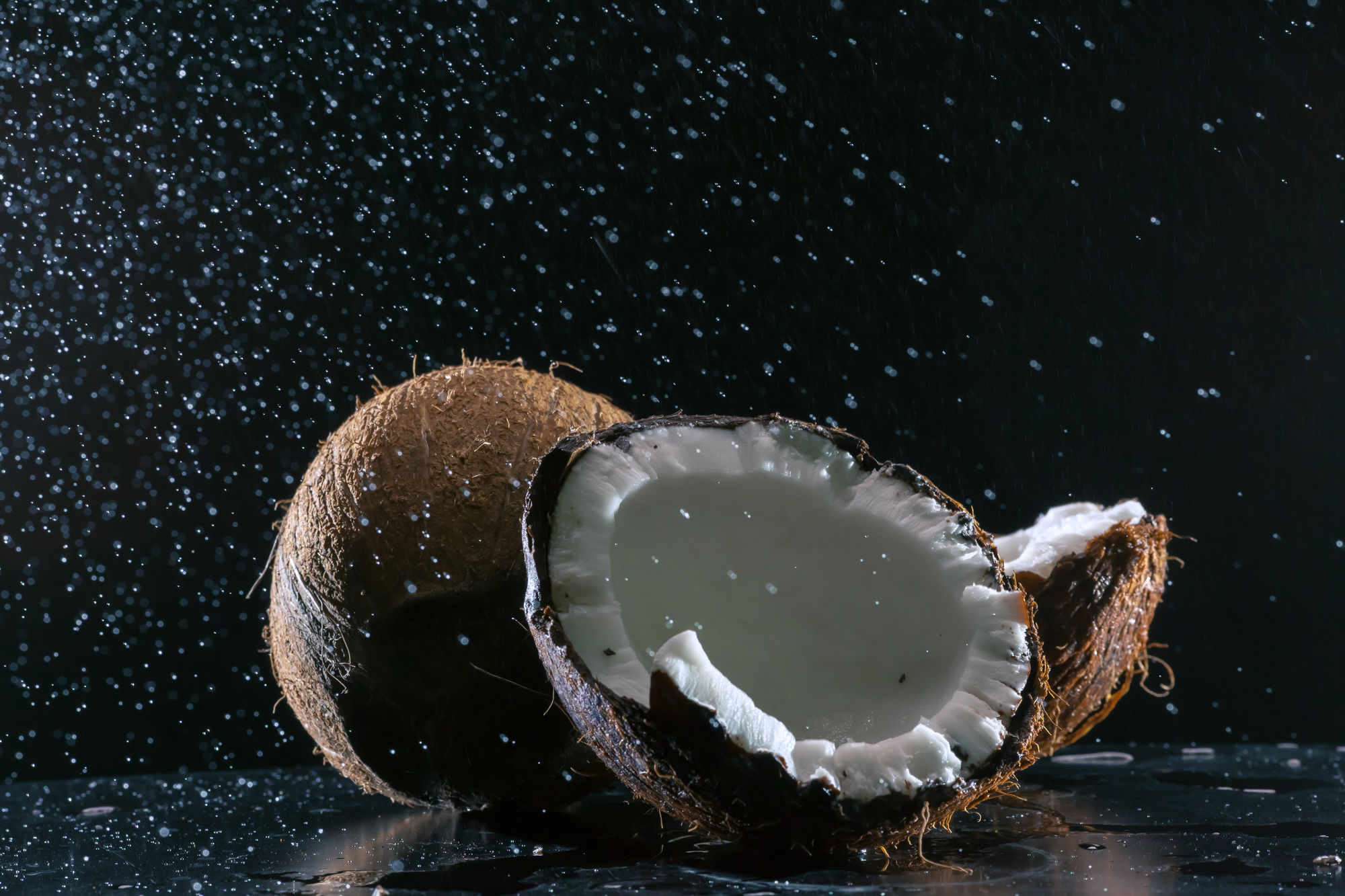 cracked coconut with big splash on black background