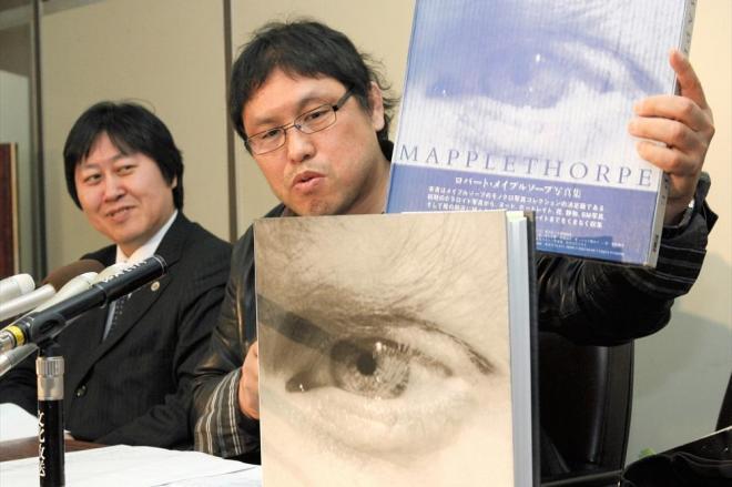 最高裁判決後の記者会見で、メイプルソープ写真集を手にする原告の浅井隆さん... 最高裁判決後の記