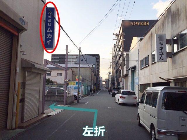【道順3】しばらく直進すると、向かって左側に「株式会社ムカイ」の建物看板が見えますので、その建物の隣が駐車場です。矢印方向に左折してください。