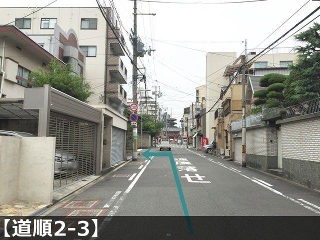 【道順2-3】1つ目の信号手前で左側にある建物にご利用駐車場がございます。ご予約されたスペースに駐車してください。