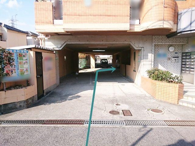 【順路1】駐車スペースはマンション入口左側の通路を通った先にあります。ご予約された駐車場に間違いないか確認し、ご予約されたスペースに駐車してください。