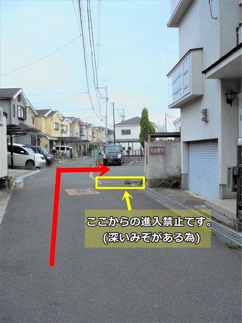 黄色の枠の場所は深いみぞがあるため進入禁止です。赤の矢印の位置から駐車場に入ってください。