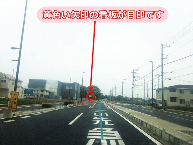 【道順6】前方左側に見える「黄色い矢印の看板」が駐車場の目印です。