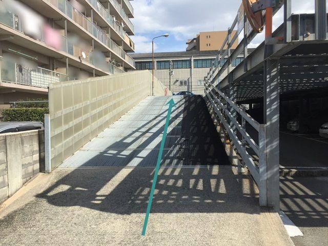 【道順9】こちらのスロープを上ると駐車スペースがあります。ご予約時のメールに記載しているスペース番号をしっかりとご確認のうえ駐車して下さい。
